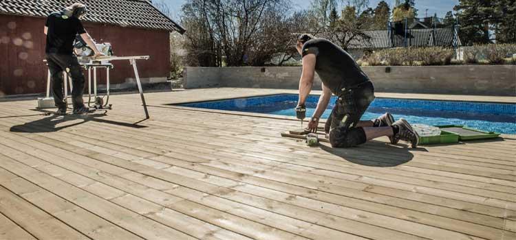 Pemasangan decking kayu di samping kolam renang
